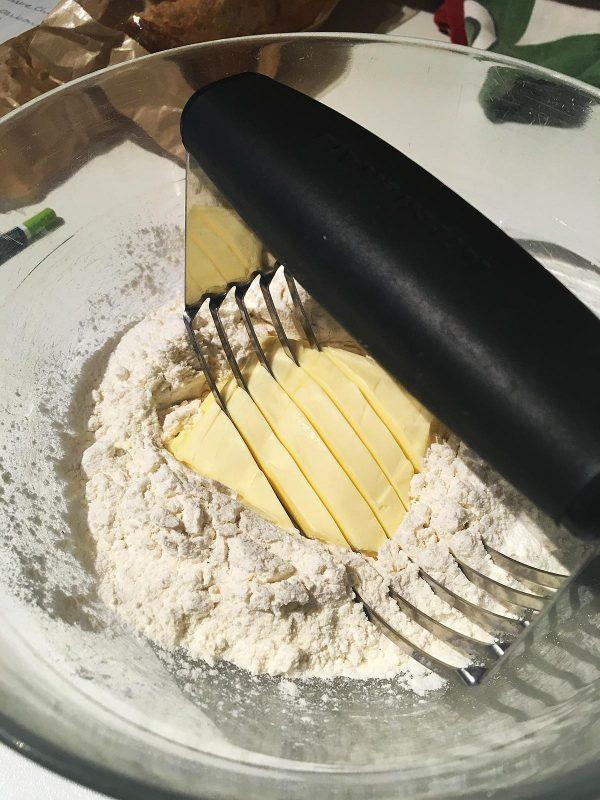 Coupez le beurre avec le mélange de farine, sel et poudre à lever, jusqu'à l'obtention d'une texture de sable humide, avec des petits morceaux de beurre uniformes.