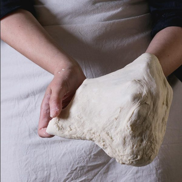 """Pour étaler une pizza, placer chaque moitié de la pâte sur un grand morceau de papier de cuisson . Former en disc avec vos mains et placer sur le papier. Ensuite, commençant du milieu et travaillant vers l'extérieur du cercle étale la pâte. Pour une pâte """"épaisse"""" 50mm est bon. Pour la pâte fine, utiliser un rouleau pour étaler sans faire des trous . Si la pâte se retire, laisser reposer 5 minutes avant de continuer."""